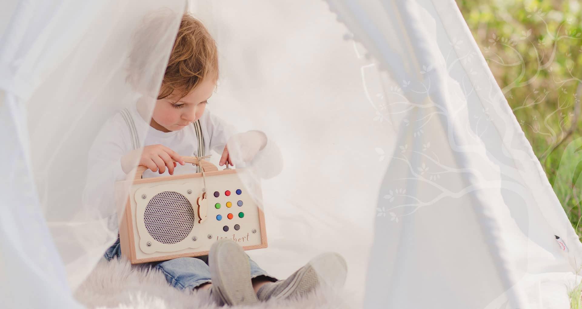 Kind draussen im Zelt mit seinem Musikspieler